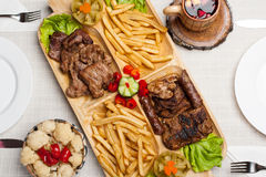 Mix grilled with meat, wine, fries potatoes Stock Photography