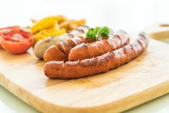 Mix grilled sausage with vegetables and french fries. On wood board Stock Image