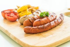 Mix grilled sausage with vegetables and french fries. On wood board Royalty Free Stock Photos