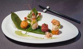 Mix of gunkan maki, asian fusion cousine. With tuna, salmon, caviar, swordfish, rice, prawn, cucumber, ginger gari and wasabi Royalty Free Stock Photos