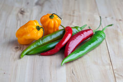 Mix of hottest peppers on wooden table. Royalty Free Stock Photo