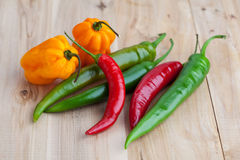 Mix of hottest peppers on wooden table. Stock Photos