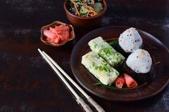 Mix of Japanese food - rice balls onigiri, omelette, pickled ginger, sunomono wakame cucumber salad and chopsticks. Asian. The mix of Japanese food - rice balls royalty free stock photo