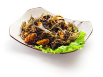 Mix from kelp, mussel and salad. On the squared plate over white background Royalty Free Stock Images