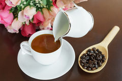 Mix milk into a cup of coffee Stock Photo
