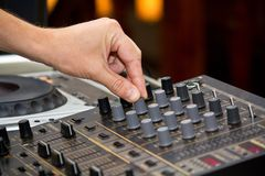 Mix the music. Image of a hand adjusting the settings of an audio mixer Royalty Free Stock Image