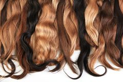 Mix of natural extensions hair: blond, red, brown. Strands of ha Royalty Free Stock Photos