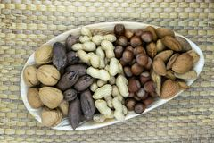 Mix of the Nuts. Almonds, Pecans, Hazelnuts, Walnuts, Peanuts pl. Aced in eco natural banana leaf plate on natural bamboo tat with free space Royalty Free Stock Photo