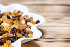 Mix of nuts and berries. Dried fruits in white plate on wooden table, copy space for text. Healthy food and vitamins. Mix of nuts and berries. Dried fruits in royalty free stock photos