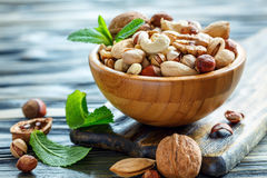 Mix nuts in a bowl closeup. Mixed nuts in a wooden bowl on old table, selective focus royalty free stock images
