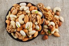 Mix of different nuts in a wooden cup against the background of fabric from burlap. Nuts as structure and background, macro. Top. Mix of nuts of cashew, almonds stock photo