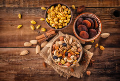 Mix of nuts and dried fruits. On a old rustic table. gold pistachios, cashews, hazelnuts, almonds. Top view royalty free stock photo