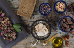 Mix of nuts and herbal, Aleppo soap and shea butter. Mix of herbs, flower, argan nut and oil, shea nuts and butter, anise and Aleppo soap on wooden table Stock Photography