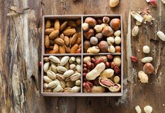 Mix of nuts: pistachio, almonds, hazelnut, peanuts in vintage wooden box on rustic wooden background. Top view. Raw healthy food. stock photography