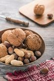 Mix of nuts on a vintage plate on the background of the old table stock image