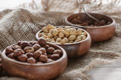 Mix of nuts in wooden bowls. On sackcloth stock photo