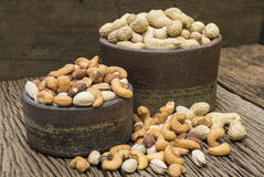 Mix nuts on a wooden table. Pigeon peas mixed nuts such as pistachios, peanuts, cashews and almond on a wooden table Royalty Free Stock Photo