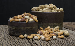 Mix nuts on a wooden table. Pigeon peas mixed nuts such as pistachios, peanuts, cashews and almond on a wooden table Stock Photo