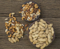 Mix nuts on a wooden table. Pigeon peas mixed nuts such as pistachios, peanuts, cashews and almond on a wooden table Royalty Free Stock Image