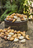 Mix nuts on a wooden table. Pigeon peas mixed nuts such as pistachios, peanuts, cashews and almond on a wooden table Stock Image