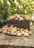 Mix nuts on a wooden table. Pigeon peas mixed nuts such as pistachios, peanuts, cashews and almond on a wooden table Royalty Free Stock Photography