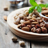 Mix of nuts on the wooden table. Selective focus and square image Royalty Free Stock Photos