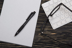Mix of office supplies and gadgets on a wooden background. Royalty Free Stock Photos