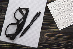 Mix of office supplies and gadgets on a wooden background. Stock Image