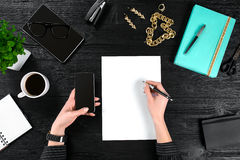 Mix of office supplies and gadgets on a wooden desk background. View from above. Royalty Free Stock Photography