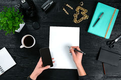 Mix of office supplies and gadgets on a wooden desk background. View from above. Stock Photos