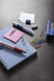 Mix of office supplies on a wooden desk background. Royalty Free Stock Image