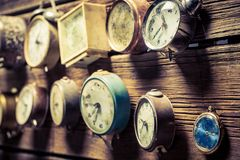 Mix of old clocks on the wooden wall. Closeup of mix of old clocks on the wooden wall royalty free stock images