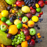Mix of  Organic Fruits  with water drops on dark wooden table Royalty Free Stock Photography