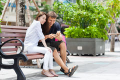 Mix race couple using cell smart phone sitting in Royalty Free Stock Image