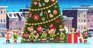 Mix race elves group near decorated fir tree city building houses night winter street cityscape merry christmas happy stock illustration