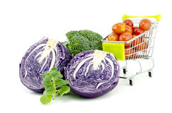 Mix of raw and fresh vegetables.purple cabbage, cherry tomatoes on trolley, green mint and broccoli. Isolated white background Royalty Free Stock Images
