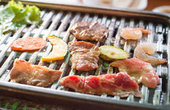 Mix raw meat grilling on grill grate Royalty Free Stock Images