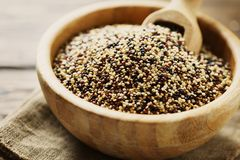 Mix of raw red, white and black quinoa on thw wooden table Stock Image