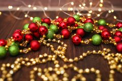 Mix of red, green, and golden Christmas balls. New Year decor for tree on dark wooden background.  royalty free stock image