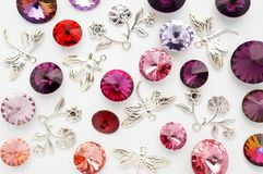 Red and pink crystals and metal bees and flowers and dragonflies on white background Royalty Free Stock Photography