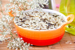 Mix rice in the orange bowl. Mix raw rice in the orange bowl with oil and flower Stock Photo