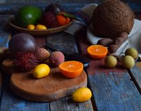 Mix of ripe tropical fruits with passion fruit, kumquat, lychee, rambutan, tamarind, avocado, coconut, dragon eye on a wooden back Stock Photos