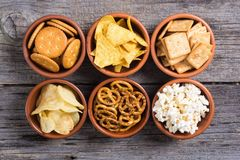 Mix of snacks. Frame . Mix of snacks : pretzels , crackers , chips , pop corn and nachos stock images