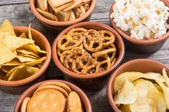 Mix of snacks. Frame . Mix of snacks : pretzels , crackers , chips , pop corn and nachos stock photo