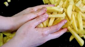 Mix spices with long raw fries potatoes by hands