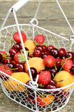 Mix of summer fruits and berries in wire basket Stock Photo