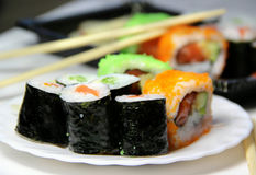 Mix of sushi specialties. Sushi specialties and wooden chopsticks Royalty Free Stock Images