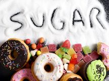 Mix of sweet cakes, donuts and candy with sugar spread and written text in unhealthy nutrition. Chocolate abuse and addiction concept, body and dental care stock photography