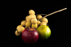 Mix thai fruit. A bunch of Longan ,an Apple and an Orange in black background Stock Images