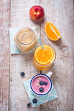A mix of three smoothies with blueberry, orange and peach on a wooden background Stock Images